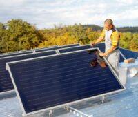Ein Monteur installiert auf einem Flachdach Solarthermie-Kollektoren.