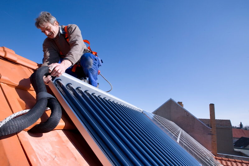 Ein Installateur montiert auf einem Spitzdach mit roten Schindeln einen blauen Solarwärmekollektor.