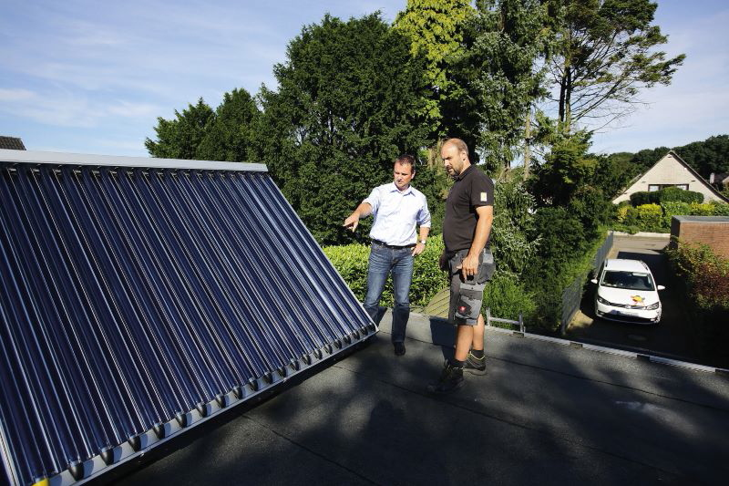 Ein Monteuer bespricht sich auf dem Dach mit dem Eigentümer über die Installation von Solarkollektoren.