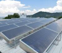 Auf einem Industriedach stehen Solarthermiekollektoren und ein Wasserspeicher. Im Hintergrund grüne Hügel.
