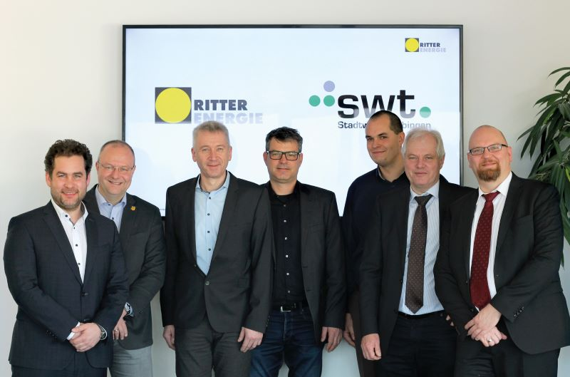 T Herren in Anzügen vor einem Bildschirm, der eine Präsentation der Stadtwerke Tübingen und Riter Energie zeigt.