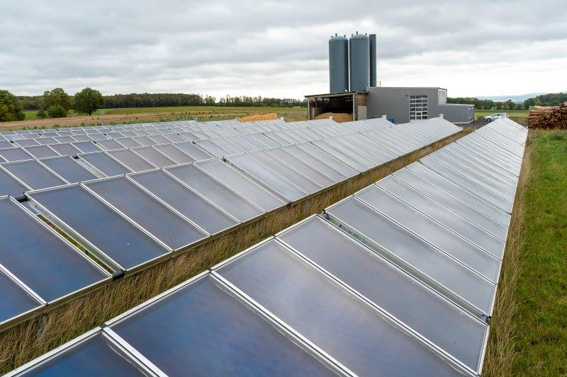 Eine Reihe von Solarthermiekollektoren im Freien vor einer regionalen Heizzentrale.
