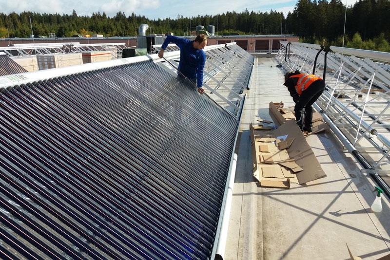 Montage eienes großen Solarkollektors auf einem Fabrikdach.