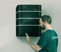 """Solarwatt-Mitarbeiter kontrolliert wandhängenden BMW_Solarwatt-Speicher """"Battery flex"""","""