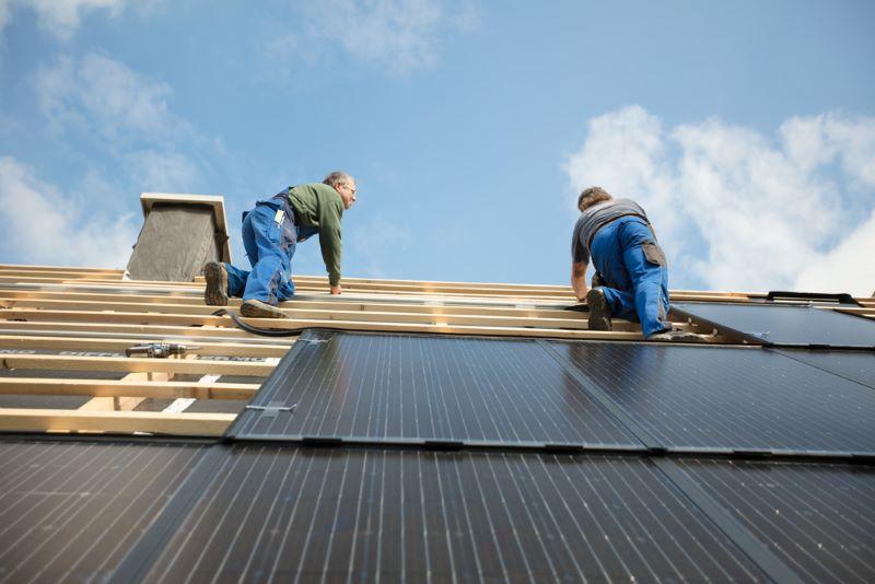 Zwei Arbeiter installieren PV-Module auf einem Spitzdach.