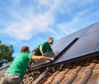 Arbeiter installieren auf einem Spitzdach neue Solarstrommodule.