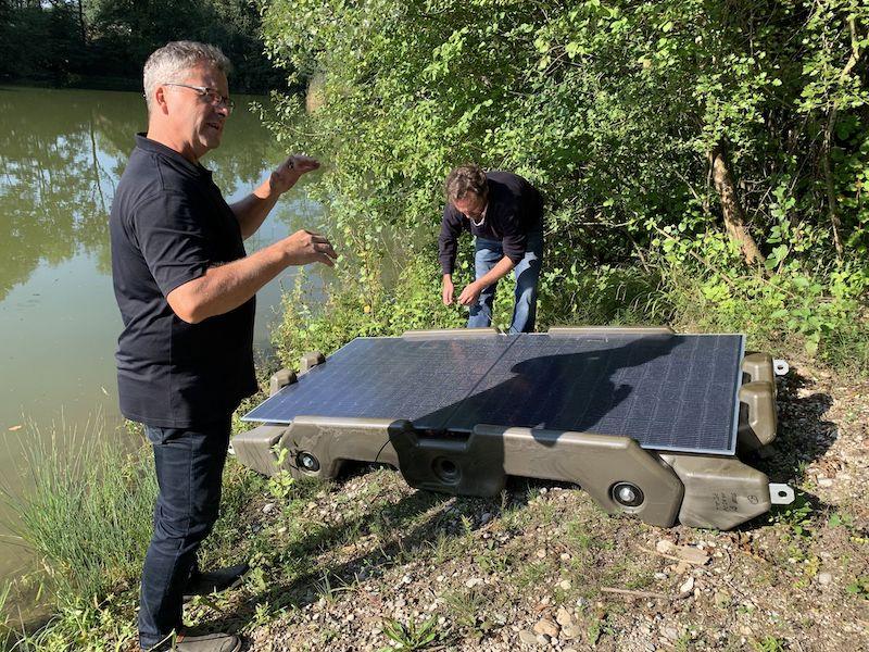 Zwei Männer und zwei Photovoltaik-Module auf einer Kunststoff-Konstruktion am Ufer - die Floating-PV-Anlage geht in den Test.