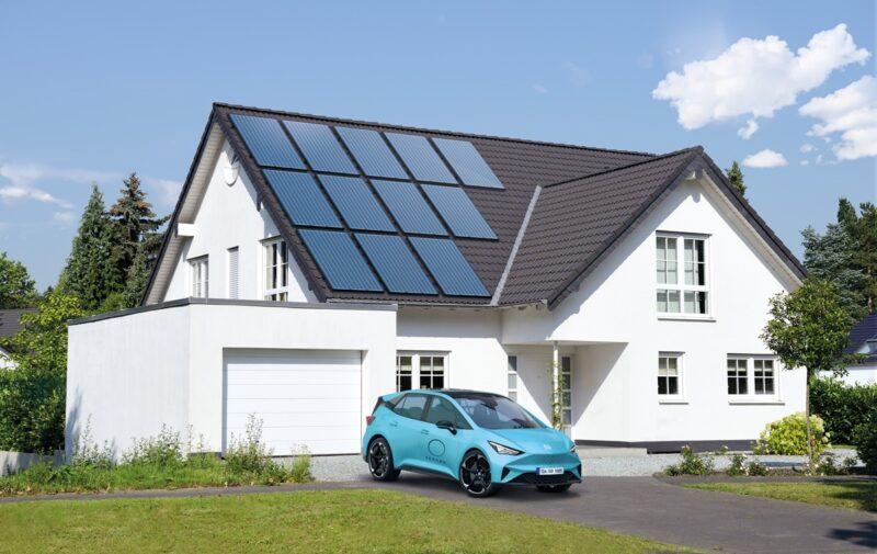 Das Bild zeigt ein großes Einfamilienhaus mit Photovoltaik-Anlage auf dem Dach und einem Elekotrauto vor dem Haus.