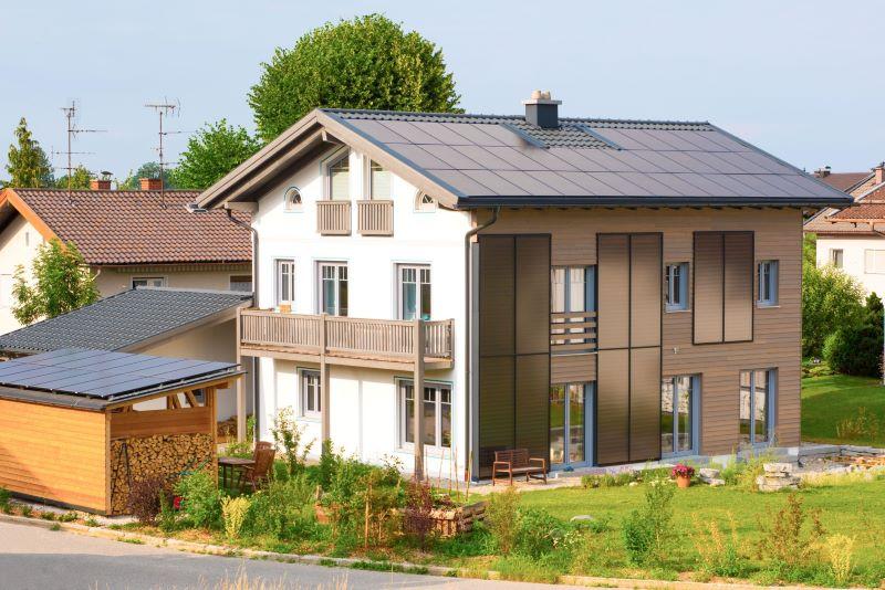 Einstöckiges Einfamilienhaus mit Solarthermieanlage an Dach und Fassade.