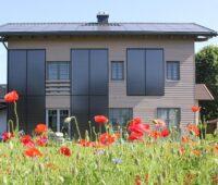 Zu sehen ist ein Gebäude mit Sonnenkollektoren an der Fassade. Die Einschätzung, dass Solarthermie nur auf geneigten Süddächern funktioniert, gehört ebenfalls zu den Irrtümern über die Solarthemrie.