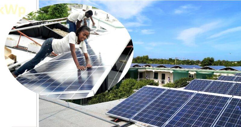 Zu sehen ist eine Photovoltaik-Anlage der Biohaus-Stiftung auf Haiti und Menschen bei der Wartung.