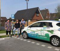 Die Mieterin Silke Schladetzky steht mit der hauseigentümerin udn dem Projektleiter der Husumer Stadtwerke an der Ladesäule für Elektroautos.