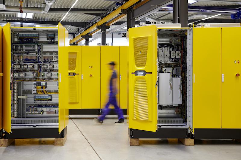 Gelbe Schaltschränke in einer Fertigungshalle der Schaper Gruppe, die gerade Batterie-Speicher von Tesvolt für Wasserstoff-Projekte eingekauft hat.