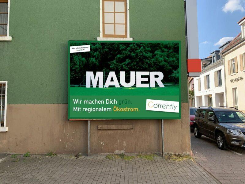 Zu sehen ist ein Plakat an einer Mauer in Mauer, das auf den Ökostromtarif Corrently hinweist.
