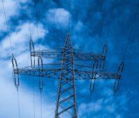 Ein Strommast vor baluem Himmel udn einzelnen Wolken.