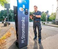 Ein Mitarbeiter der Stadtwerke Bonn checkt eine Ladesäule an einer Straße.