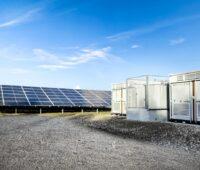 Zu sehen sind die Container, die die Wechselrichter für den Photovoltaik-Solarpark Weesow-Willmersdorf enthalten. Sie stehen zwischen den Photovoltaik-Modulen.