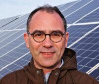 Portrait Sven Neunsinger vor Photovoltaik-Freiflächenanlage in Tunesien.