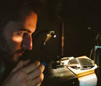 Ein Wissenschaftler betrachtet eine beleuchtete Solarzelle.
