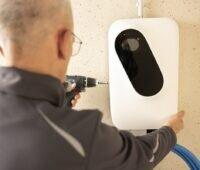 Zu sehen ist ein Monteur der die Ladebox für Elektroautos des Pakets Charging by EnOSTM installiert.