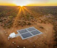 Luftaufnahme von PV-Anlage in Australien mit roter Erde und untergehender Sonne,mit Tesvolt-Batterie-Speicher
