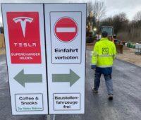 Ladepark Hilden: Zu sehen ist ein Schild, das zu den provisorisch aufgestellten Tesla-Superchargern führt.