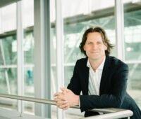 Timo Leukefeld vor einer Glasfassade