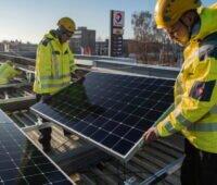 Arbeiter installieren Solarmodule auf einem Tankstellendach.