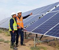 Zwei Arbeiter mit Signalwesten vor Photovoltaikmodulen Eines PV-Parks in Tunesien