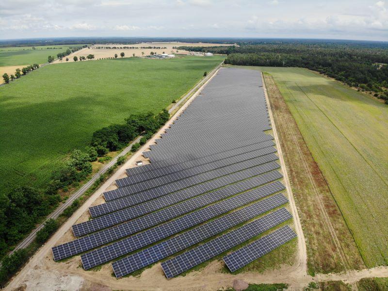Luftaufnahme eines Freiflächensolarparks in landwirtschaftlich geprägter Umgebung.