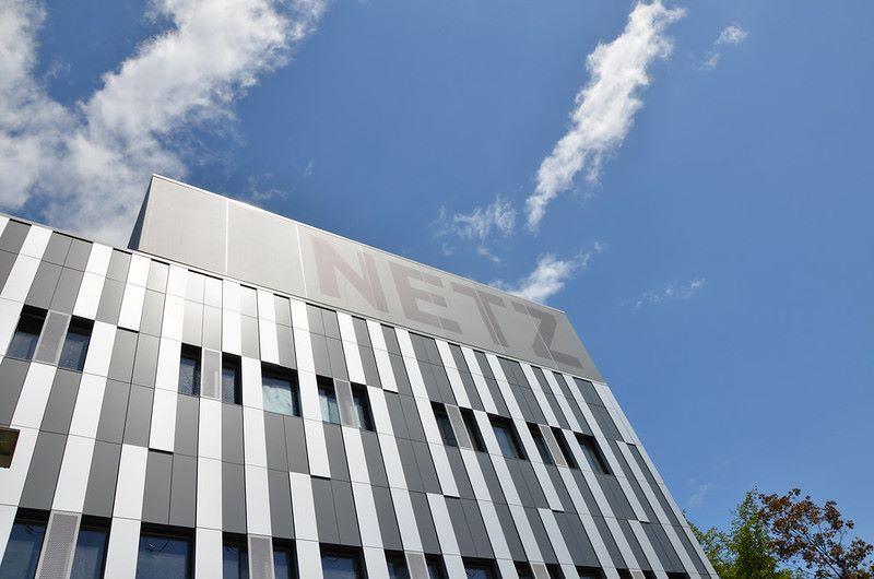 Gebäude mit moderner silberner Fassade und dem Schriftzug Netz gegen blauen Himmel.
