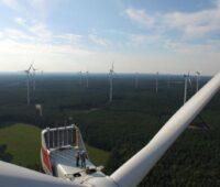Ein Windpark in Deutschland von oben. Auf einer der Gomdeln stehen zwei Menschen