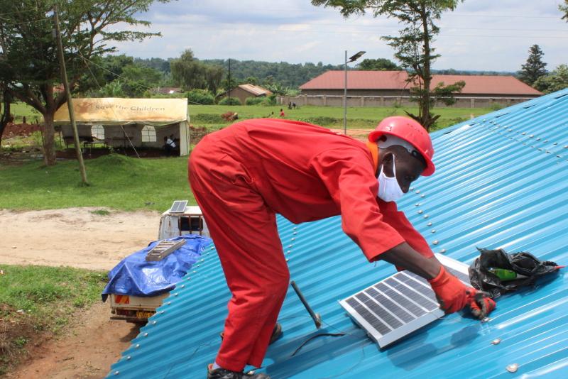 Ein Mann im roten Overall installiert auf einem Wellblechdach in Uganda ein Solarmodul.