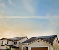 Spitzdächer mit Solaranlagen unter blauem Himmel zum Sonneaufgang.