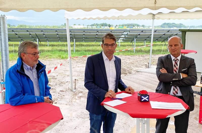 Vorne drei Männer, dahinter die Photovoltaik-Anlage, ganz hinten eine Reihe LKW auf der Autobahn