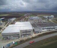 Luftbild neuer Fabrikgebäude in einem Gewerbegebiet an der Autobahn.