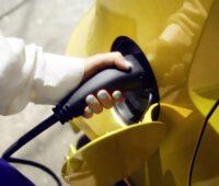 Zu sehen ist eine Frauenhand die das Ladekabel eines E-Autos hält. Ladeinfrastruktur für Elektroautos in Mehrfamilienhäusern braucht Förderung.