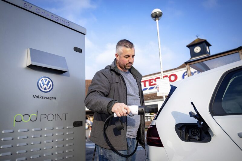 Das Foto zeigt einen Mann beim Laden seines Elektroautos.