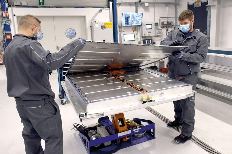 Zwei Mitarbeiter demontieren eine Fahrzeubatterie bei VW