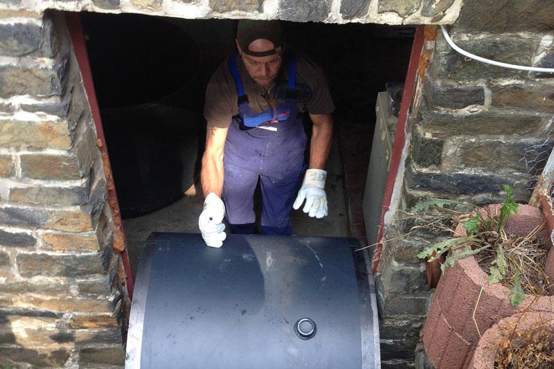 Zylinderförmiges Speichersegment wird von einem Handwerker durch eine schmale Kellertür bugsiert