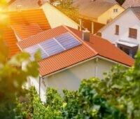 Zu sehen ist ein Hausdach mit Photovoltaik-Anlage. Ein digitaler Wegweiser für Betreiber von Ü20-Solaranlagen hilft weiter.