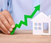 Zu sehen ist ein symbolisches Bild, nach oben zeigende Kurve über einem Haus, für steigende Energiekosten.