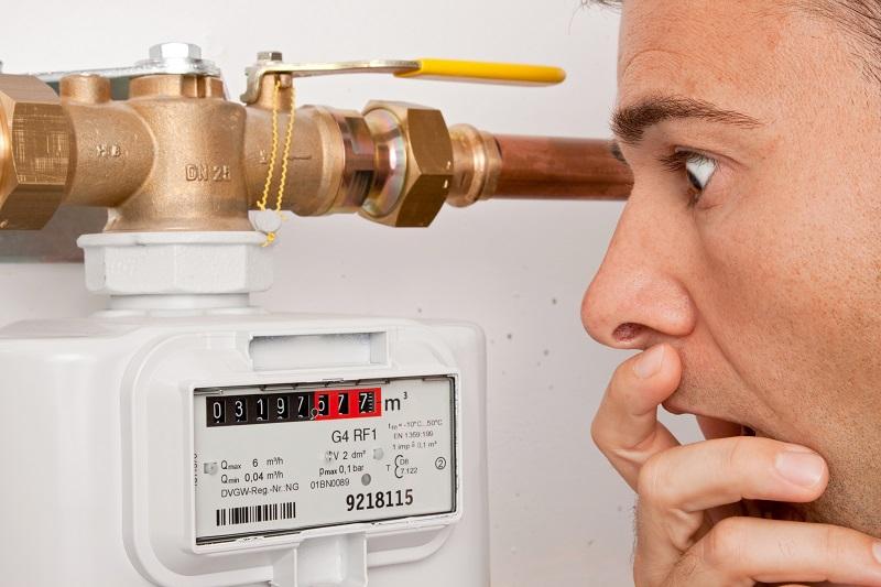 Zu sehen ist ein Mann, der entsetzt auf den Gaszähler schaut und dabei wohl die steigenden Gaspreise im Kopf hat.