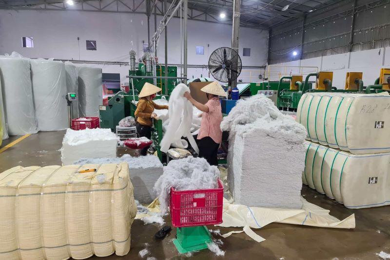 Zwei asiatische Frauen hantieren mit Polyester unf Baumwolle in einer Textilfabrik.
