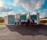 16 Personen vor einem Batteriespeicher, der in Containern untergebracht ist, unter blauem Himmel mit Wolken.