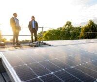 2 Männer im Gespräch auf einem Flachdach mit Photovoltaik.