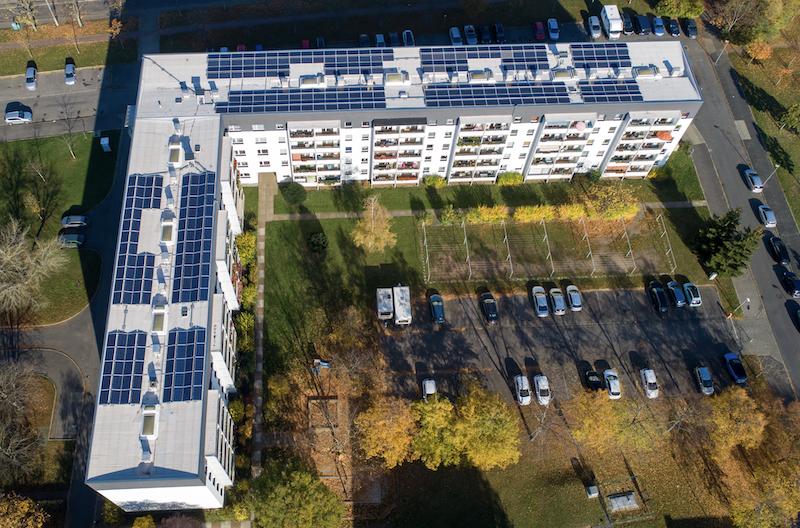 Luftfoto von L-förmigem Mehrfamilienhaus, mit Photovoltaik-Anlage auf dem Dach - Vonovia erzeugt Solarstrom in Dresden.