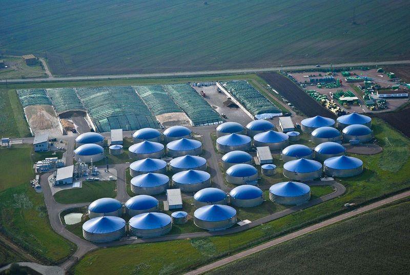 Luftbild mit zwei Dutzend blauen Biogasfermentern in grüner Wiesenlandschaft.
