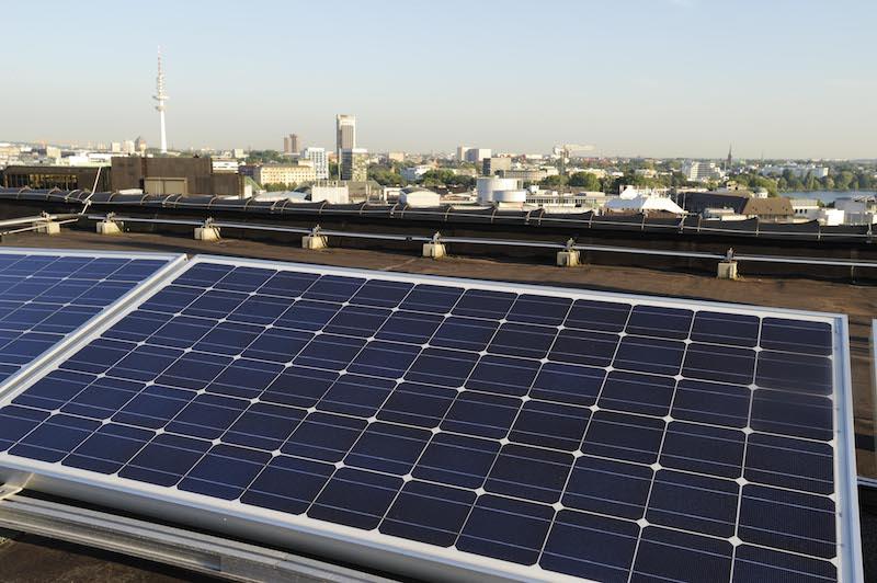 Photovoltaikanlage im Vordergrund, im Hintergrund die Skyline von Hamburg
