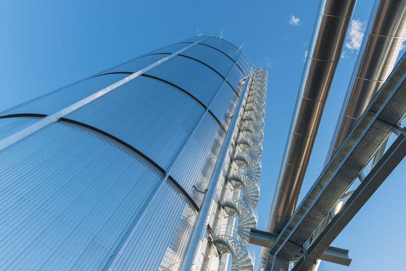 In den Himmel ragt ein technischer Baukörper, ein Großspeicher für Wärme. Rechts vom Wärmespeicher führt eine Wendeltreppe nach oben. Ganz rechts im Bild Wärmeleitungen.